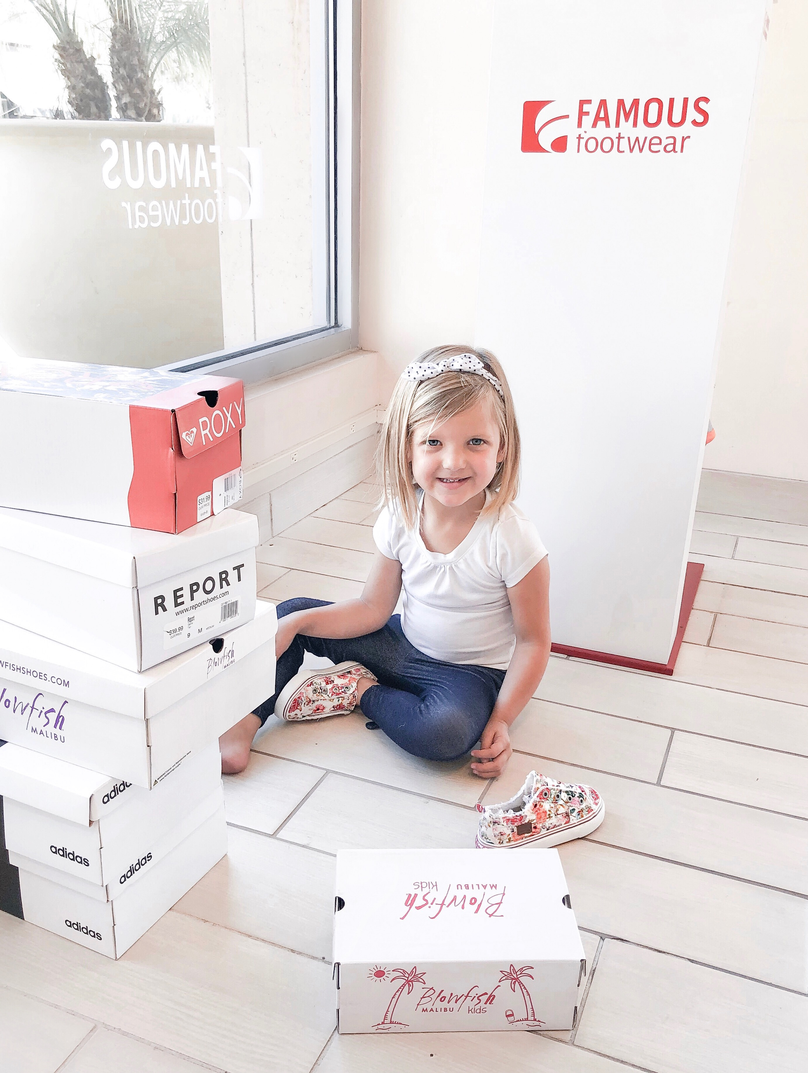 Back To School Shoes from Famous Footwear by popular San Diego fashion blog, Domestic Blonde: image of a young girl sitting on the floor at Famous Footwear surrounded by piles of stacked shoes boxes.