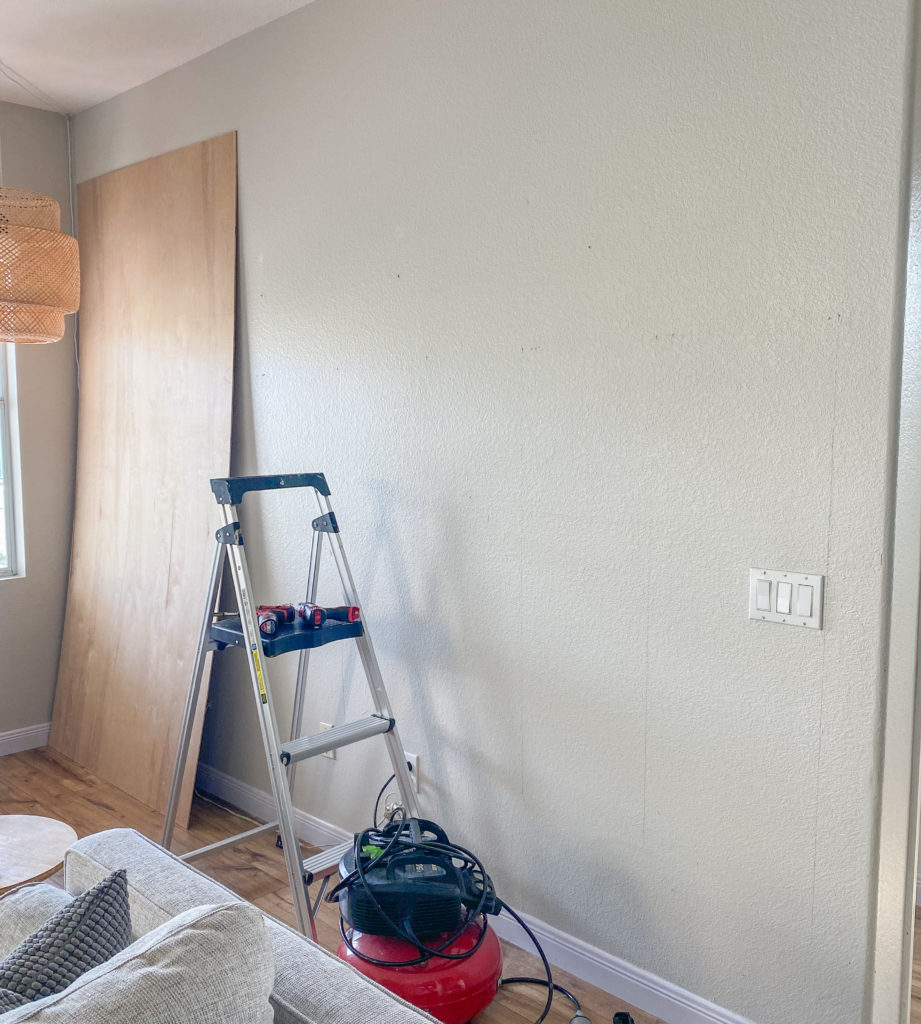 Board and Batten Wall by popular San Diego DIY blog, Domestic Blonde: image of a grey wall a step ladder, some plywood boards, and a a sander.