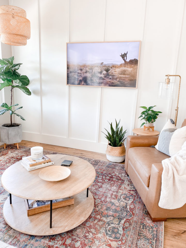 Board and Batten Wall by popular San Diego DIY blog, Domestic Blonde: image of a room with a white board and batten wall, a camel brown leather arm chair, a round wooden coffee table, a fiddle leaf fig tree, and a framed picture of some Joshua Trees.