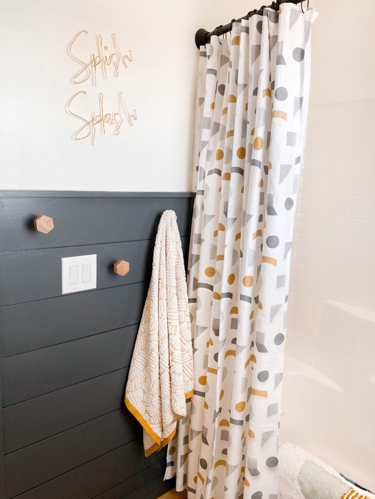 Kids Bathroom by popular San Diego interior design blog, Domestic Blonde: image of a remodeled kids bathroom with a grey shiplap wall, modern lighting, round mirror, white vanity, light wood flooring, and abstract shape shower curtain.