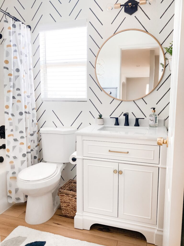 Kids Bathroom by popular San Diego interior design blog, Domestic Blonde: image of a remodeled kids bathroom with a white and grey stripe accent wall, modern lighting, round mirror, white vanity, light wood flooring, and abstract shape shower curtain.