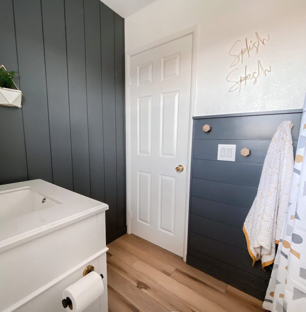 Kids Bathroom by popular San Diego interior design blog, Domestic Blonde: image of a remodeled kids bathroom with a grey shiplap wall, white vanity, light wood flooring, and abstract shape shower curtain.