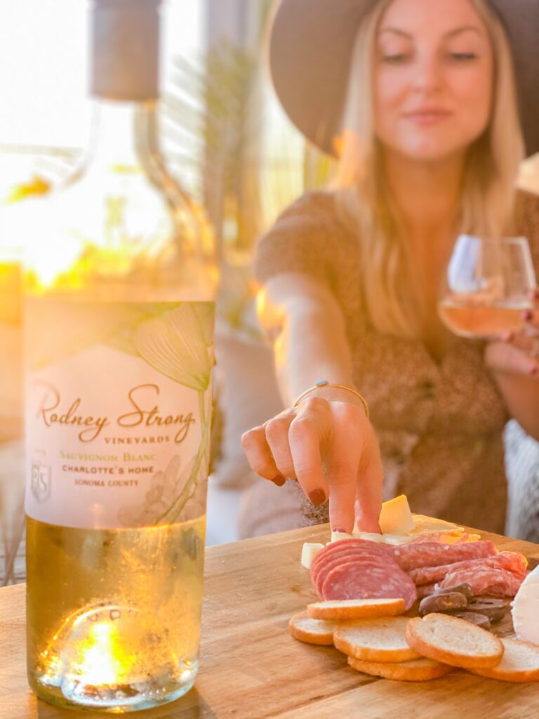 Rodney Strong Wines by popular San Diego lifestyle blog, Domestic Blonde: image of a woman holding a glass of Rodney Strong wine and eating from a charcuterie board.