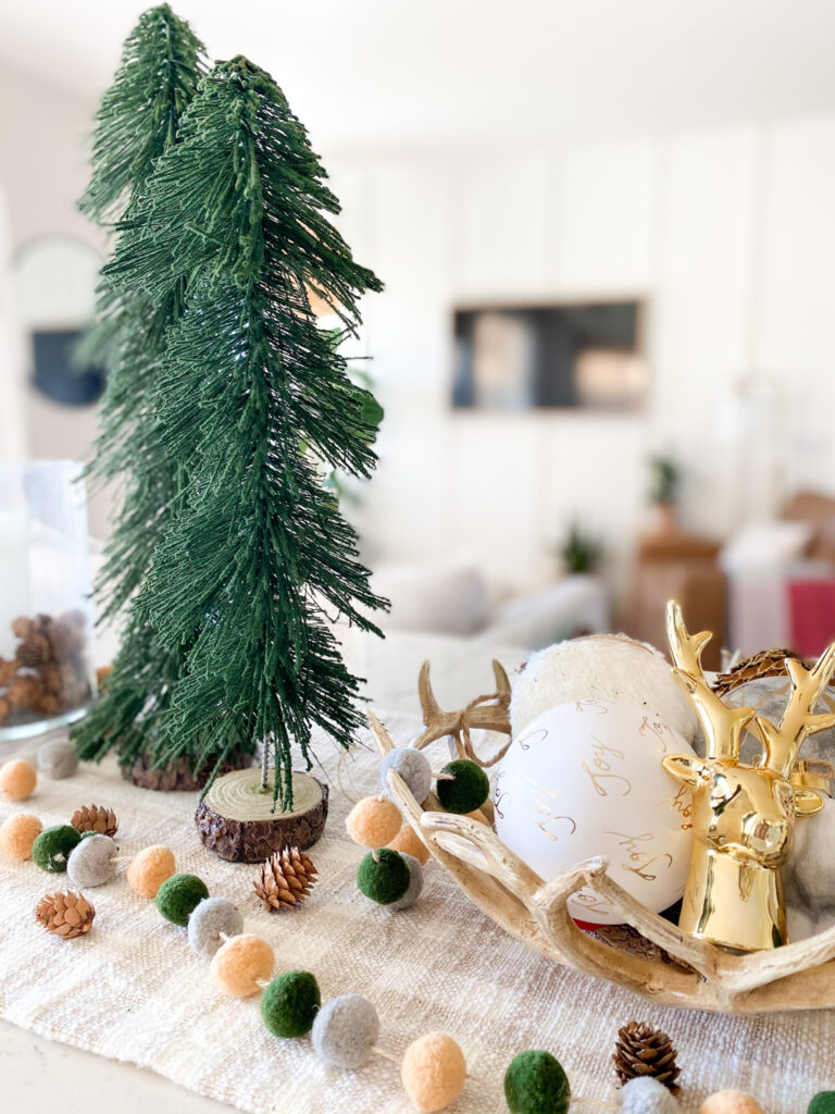 Joann Holiday Decor by popular San Diego life and style blog, Domestic Blonde: image of Joann antler bowl, white and gold ornaments, and a gold deer head and gold embossed pinecone.