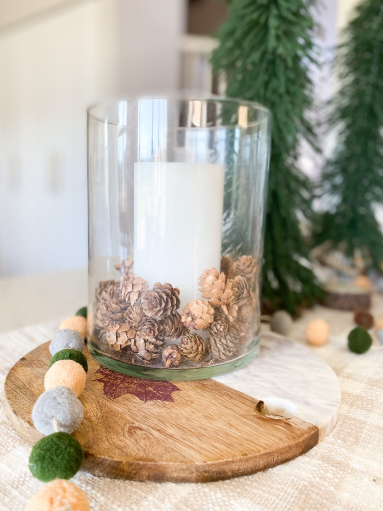 Joann Holiday Decor by popular San Diego life and style blog, Domestic Blonde: image of a wood and marble cutting board, pom pom garland, and glass jar filled with a pillar candle and mini pinecones.
