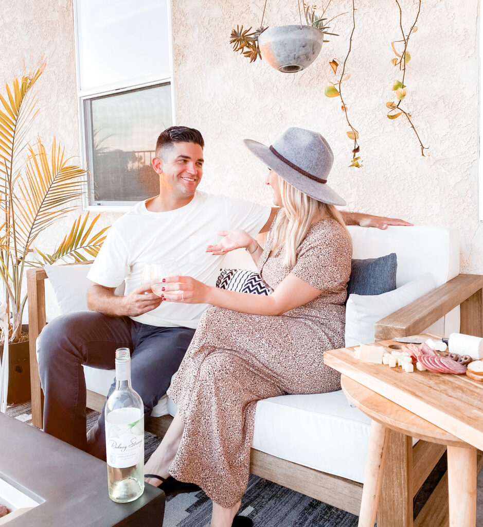Rodney Strong Wines by popular San Diego lifestyle blog, Domestic Blonde: image of a woman and her husband sitting on their back patio and drinking a glass of white Rodney Strong wine.