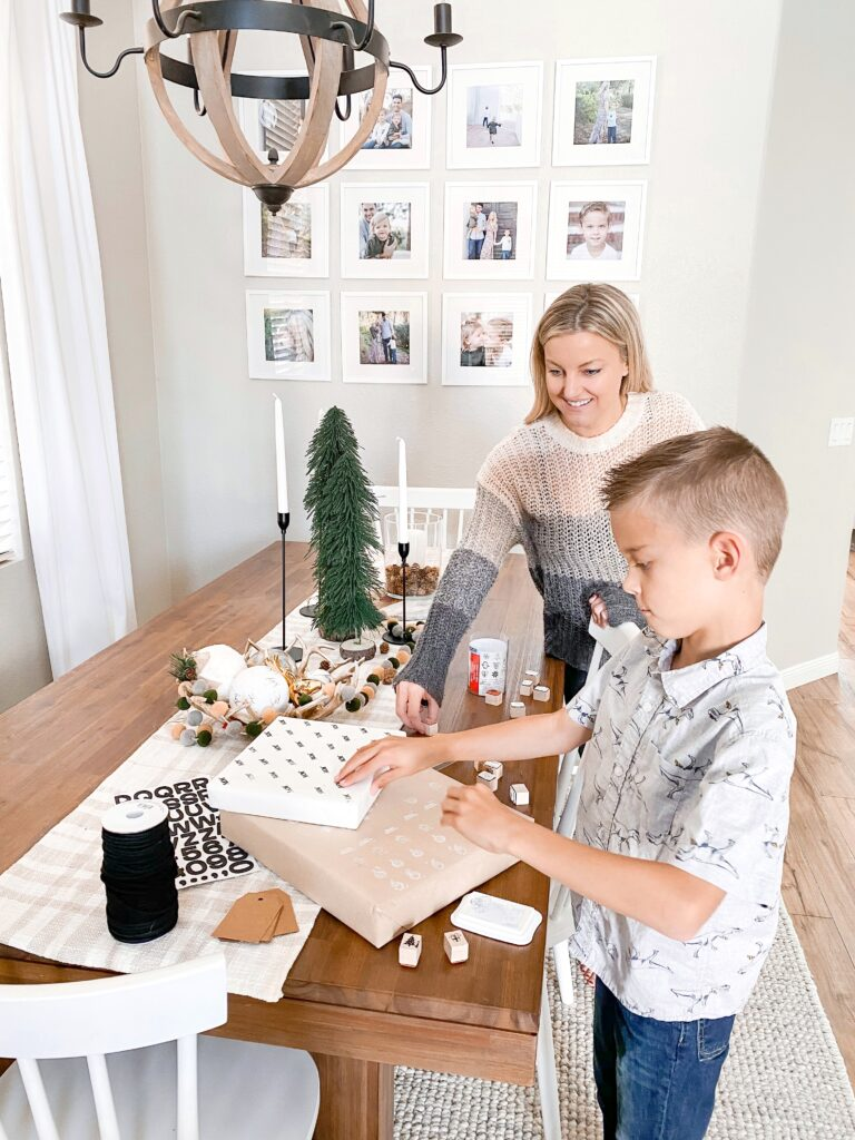 Personalized Wrapping Paper by popular San Diego DIY blog, Domestic Blonde: image of a boy and his mom stamping wrapped presents with pine tree stamps.