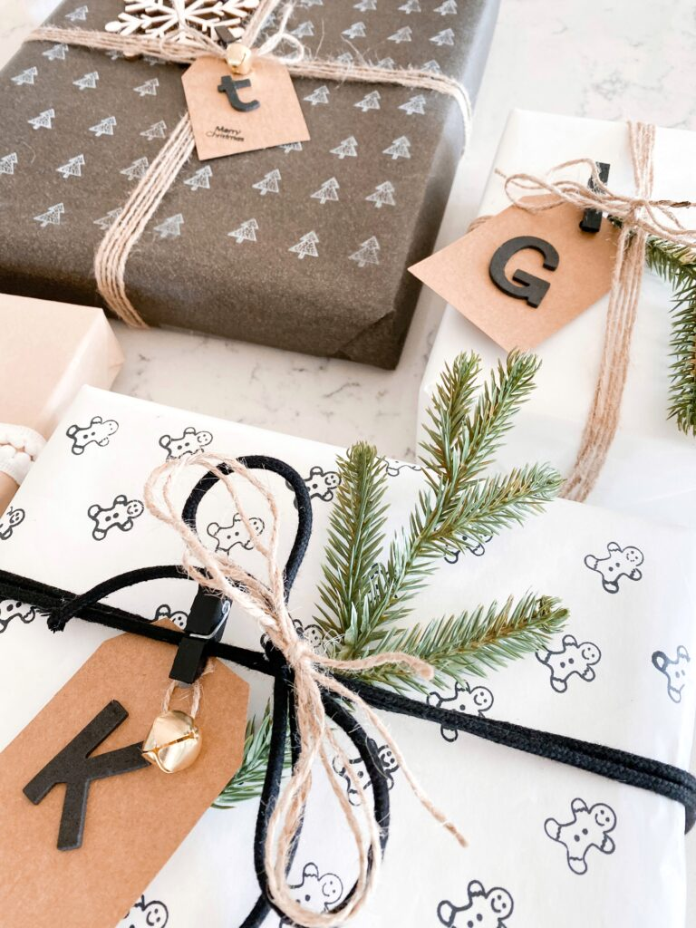 Personalized Wrapping Paper by popular San Diego DIY blog, Domestic Blonde: image of personalized presents wrapped in twine and embellished with a pine twig, wooden snowflake, and monogram gift tag.